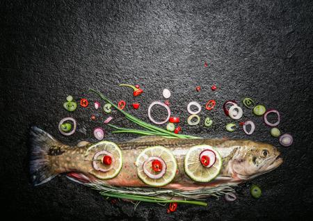 ハーブ、スパイス、暗い背景、トップ ビューで調理する魚料理の調味料で全体のマスをテキストの配置します。 写真素材