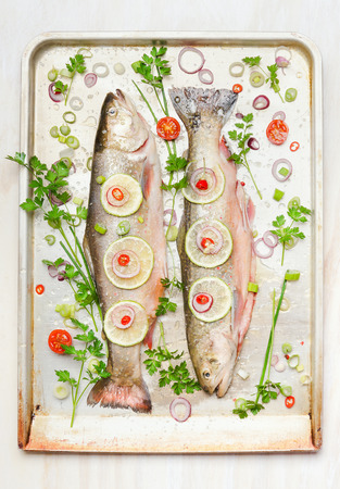 baking tray: Two whole fish with ingredients on baking pan, top view