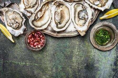 Frische Austern mit Zitrone und vaus Soßen auf rustikalen Hintergrund, Ansicht von oben, Platz für Text, Grenze