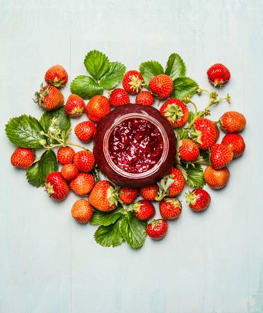jarabe: Tarro de mermelada de fresas y bayas frescas de la planta de jardín. Fresas preservación. Vista superior