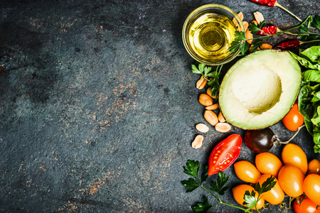 Fresh ingredients for salad or dip making: avocado, tomatoes,nuts,oil on rustic background, top view, place for text. Healthy food and cooking concept Stock Photo