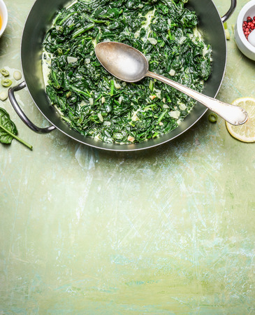 nettle: stewed spinach with cream sauce in cooking pot with spoon on rustic background, top view, place for text
