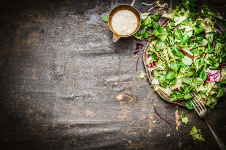 food dressing: Fresh mixed green salad with oil dressing rustic wooden background, top view. Healthy food or vegetarian eating concept. Stock Photo