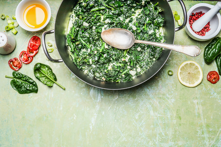 blanch: Blanch spinach with cream sauce in cooking pot with ingredients and spoon on rustic background, top view, place for text