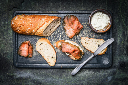 black fish: Snack sandwiches with salmon, ricotta and baguette on rustic background, top view Stock Photo
