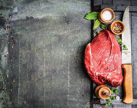 Fresh raw meat with herbs,spices and butcher knife on rustic background, top view, place for text. Cooking concept. Horizontal. Banco de Imagens