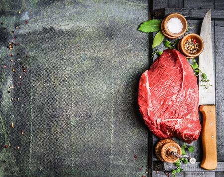 Frisches rohes Fleisch mit Kräutern, Gewürzen und Fleischermesser auf rustikalen Hintergrund, Ansicht von oben, Platz für Text. Kochen Konzept. Horizontal.