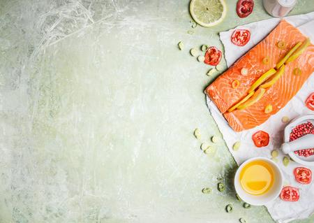 Portion de filet de saumon frais avec des tranches de citron, de l'huile et des ingrédients pour la cuisson sur un fond en bois clair, vue de dessus, place pour le texte. Concept d'alimentation ou d'alimentation saine. Horizontal