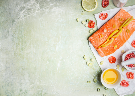 fillets: Portion of fresh salmon fillet with lemon slices, oil and ingredients for cooking on light wooden background, top view, place for text. Healthy food or diet concept. Horizontal