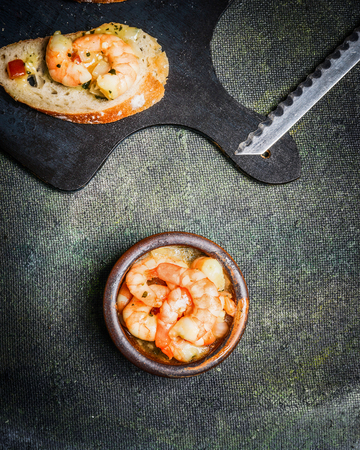 scampi: Shrimps Scampi in oil sauce in rustic bowl on dark rustic background, top view