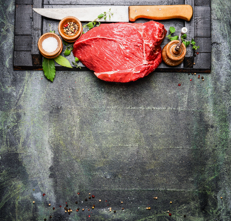 Fresh raw meat with cooking seasoning and butcher knife on rustic background, top view.