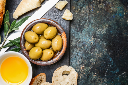 italian cuisine: Olives appetizer with cheese, oil and ciabatta gut slices on dark rustic background, top view, place for text. Italian food