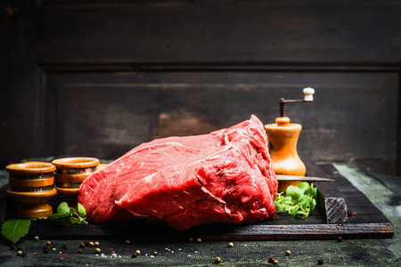 Fresh meat for tasty cooking on rustic kitchen table over dark wooden background, side view Stock Photo