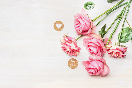 Pink roses and  round sign with message for you and heart on white wooden background, top view, place for text. Valentine Day or Birthday greeting card.