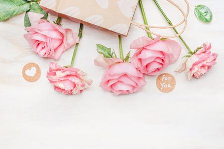ピンクの淡いバラ紙の買い物袋と心の白い木製の背景、トップ ビューでのメッセージとサインをラウンドします。バレンタインデーや誕生日のグリ 写真素材