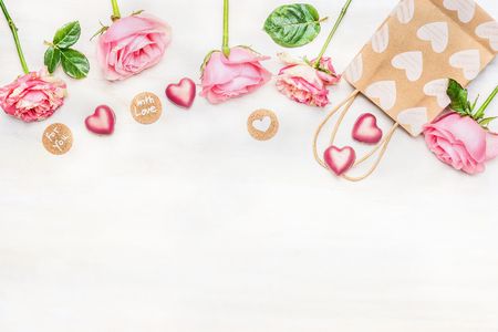 Pink roses with chocolate heart, shopping bag and round sign with message for you and with love on light background, top view.  Valentine Day or Birthday greeting card. Border. 免版税图像 - 50916269