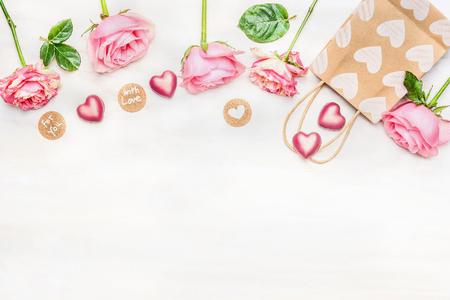 Rosa Rosen mit Schokolade Herz, Einkaufstasche und runde Schild mit Nachricht für Sie und mit Liebe auf hellem Hintergrund, Ansicht von oben. Valentinstag oder Geburtstag Grußkarte. Rand. Standard-Bild
