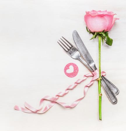 romantico: mesa de la cena lugar rom�ntico con un tenedor, cuchillo, rosa rosa y coraz�n en el fondo blanco de madera, vista desde arriba. S�mbolo del amor. D�a de San Valent�n o el concepto de cumplea�os. Foto de archivo