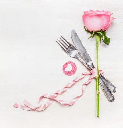 dinner: Romantic dinner table place setting with fork, knife , pink rose and heart on  white wooden background, top view. Love symbol. Valentine Day or Birthday concept. Stock Photo
