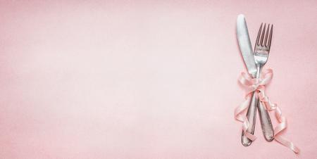 Feestelijke tabel couvert met lint decoratie op roze bleke achtergrond, bovenaanzicht, plaats voor tekst banner. Liefde, Valentijnsdag of verjaardag concept.