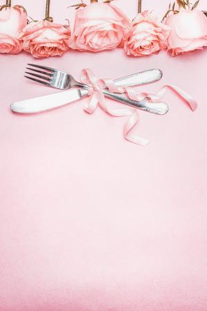 Romántico cubierto de mesa con decoración de la cinta y la frontera de las rosas en el fondo de color rosa pálido, vista desde arriba, vertical