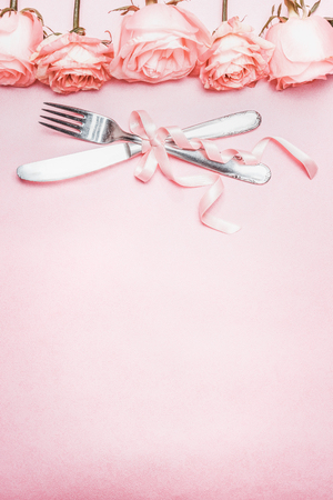 Romantic table place setting with ribbon and roses border decoration on pink pale background, top view, vertical Stockfoto