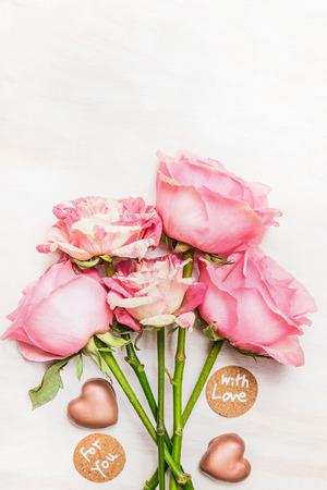 rosas blancas: rosas montón de color rosa con corazón de chocolate y la señal de mensaje con amor y para que, vista desde arriba, de cerca. día de San Valentín y el concepto de amor. día de San Valentín y el concepto de amor. Foto de archivo