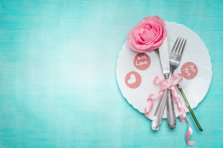 Romantic dinner table place setting with rose and sign decoration on blue background, top view. Valentines day and love concept.