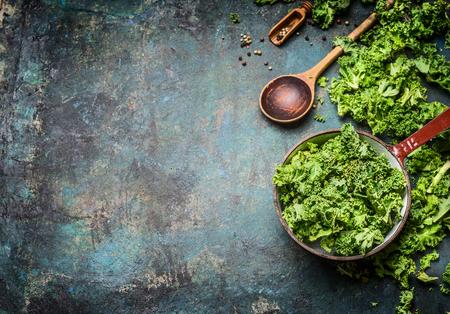 素朴な背景、平面図、国境で木のスプーンで鍋料理に新鮮なケールは。健康食品やダイエット栄養の概念。