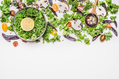 Fresh kale in cooking pot with vegetables ingredients on white wooden background, top view. Healthy food concept.