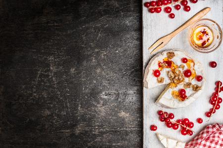 plato de comida: Queso curado camembert con las bayas y la salsa en el fondo rústico, vista desde arriba, el lugar de texto. producto lácteo leche tradicional Foto de archivo