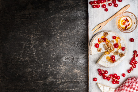 Ripened Camembert cheese with berries and sauce on rustic background, top view, place for text. Traditional milk dairy product Stock Photo