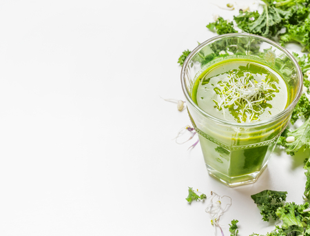 healthy nutrition: Healthy green smoothie drink in glass with kale ingredients on white wooden background, close up. Detox  nutrition and cleaning food concept.