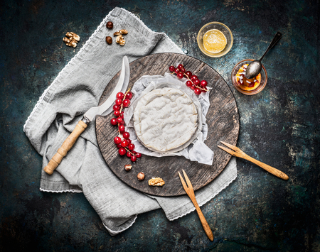 dairy product: Delicious ripe camembert cheese on wooden cutting board with berries and sauce on rustic background, top view. Traditional milk dairy product Stock Photo