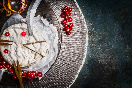 Camembert cheese plate with red currant berries and sauce on rustic background, top view, place for text. Traditional milk dairy product Stock Photo