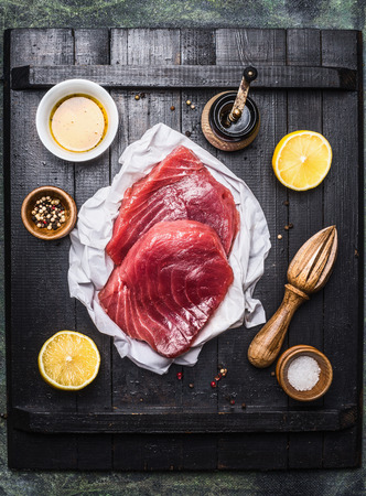 Raw tuna steak with lemon ,oil and ingredients for cooking on dark wooden background, top view Stok Fotoğraf