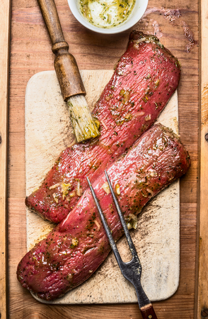 close up view: Raw fresh lamb fillet marinating for cooking or BBQ grill with brush and meat fork , top view, close up Stock Photo
