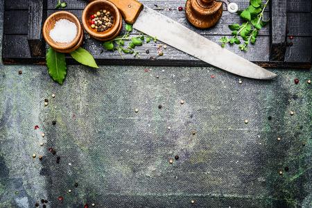 Koken set met keukenmes met tafel kruiden, zout en peper molens op rustieke achtergrond, bovenaanzicht, plaats voor tekst Stockfoto
