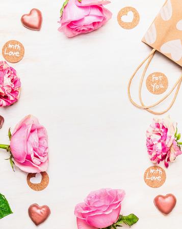 Rosas, corazón de chocolate y la bolsa de compras con las tarjetas de mensaje de amor en el fondo de madera blanco, vista desde arriba, marco. Foto de archivo - 51659240