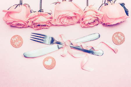 Template with festive romantic table setting, roses, ribbon, heart and love message on pink pastel background, top view