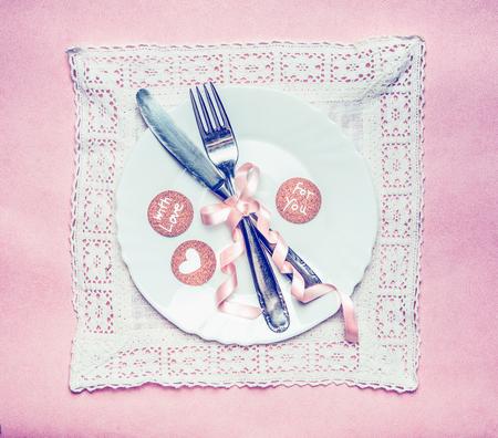 bodas de plata: mesa de la cena lugar romántico con la decoración de la cinta y tarjetas con mensajes sobre el tapete de encaje y el fondo de color rosa, vista desde arriba. Retro color entonado