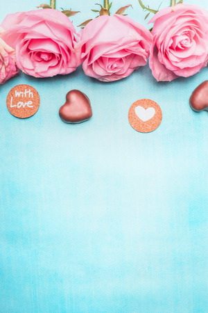 Pink roses with heart chocolate and romantic love message on blue background, top view. Valentines Day or Birthday greeting card