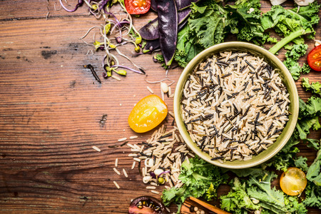 trompo de madera: Wild rice with kale and vegetables ingredients for healthy cooking on rustic wooden background, top view. Vegan and diet food concept. Foto de archivo