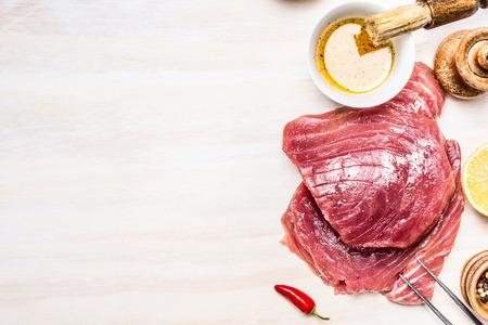 carne roja: filetes de atún con aceite y especias sobre fondo de aparentes de madera, vista desde arriba, el lugar de texto