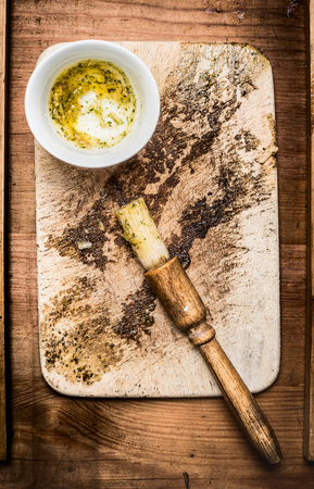 marinate: Oil marinate and brush on rustic gutting board, top view Stock Photo