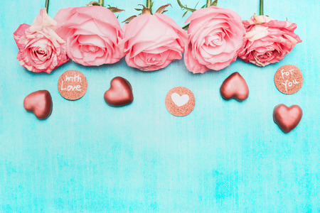 Light pink roses border with chocolate heart and love Message Sign on turquoise background, top view. Festive greeting card.