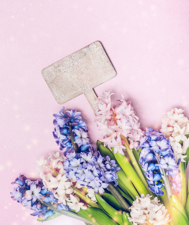 hyacinths: Bouquet of hyacinths flowers with garden wooden sign on pink background, top view, copy space