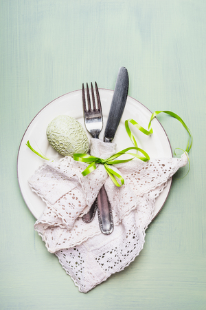over white: Easter  table place setting with cutlery and egg decoration on light green background, top view.