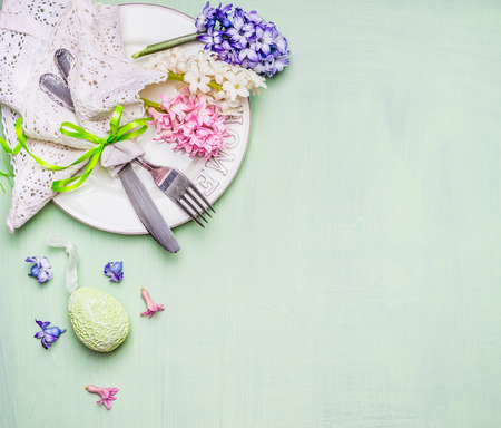 Easter  table place setting with flowers and egg on light green background, top view. Place for text or Easter meal.
