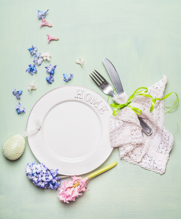 Easter  table place setting with blank plate, hyacinths flowers decoration, cutlery and decor egg on light green background, top view. Spring or Easter food concept